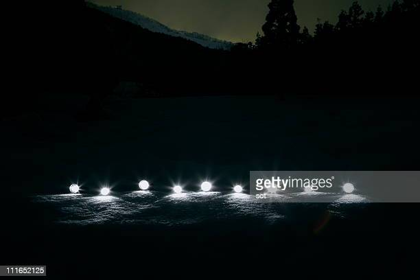Light from torches lying on the snow,at night