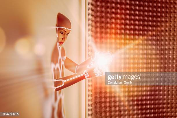 light glowing in hands of futuristic woman emerging from wall - appearance stock pictures, royalty-free photos & images
