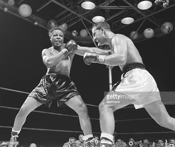 Light heavyweight champion Archie Moore lands a hard left during the fifth round of his bout against heavyweight champion Rocky Marciano at Yankee...