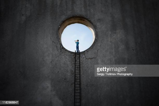 light hole in dark wall and man stands on a step ladder - escaping stock pictures, royalty-free photos & images