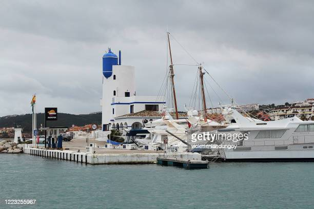 light house and boats at a marina in la linea de conception - la linea de conception stock pictures, royalty-free photos & images