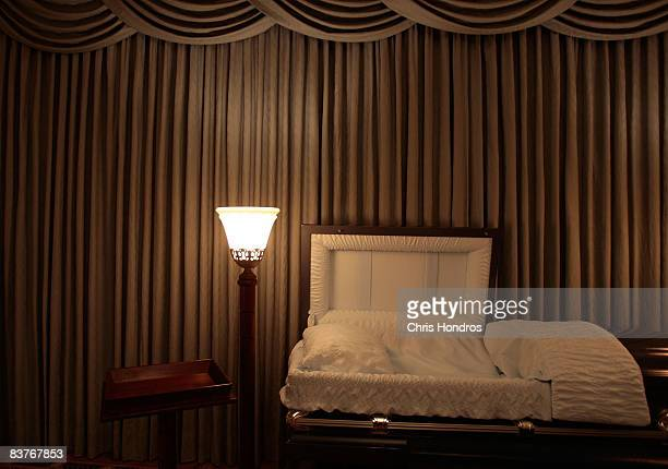 A light illuminates an empty casket in the funeral parlor of Greenwich Village Funeral Home on November 20 2008 in New York City Despite the...