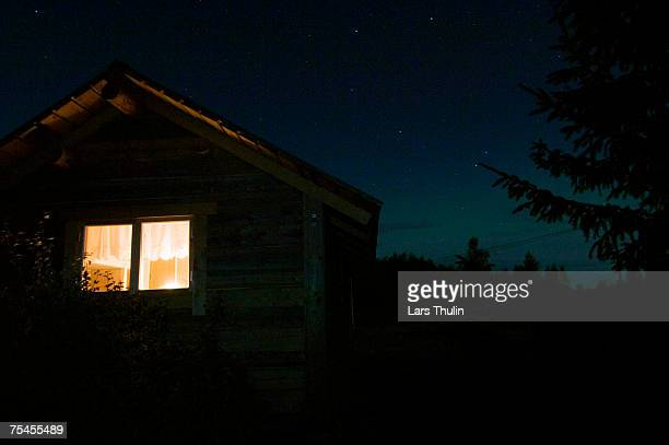 light in a window on a cottage. - verlicht stockfoto's en -beelden