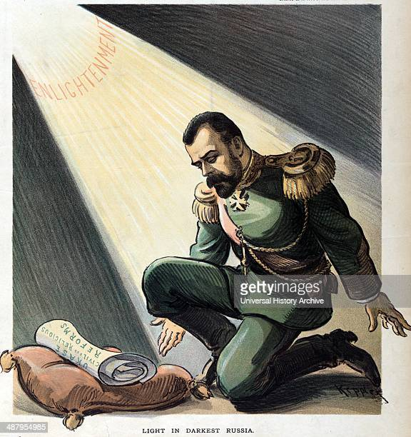 Light in darkest Russia by Udo Keppler 18721956 artist 1903 Illustration shows Nicholas II Emperor of Russia kneeling on one knee before a pillow on...