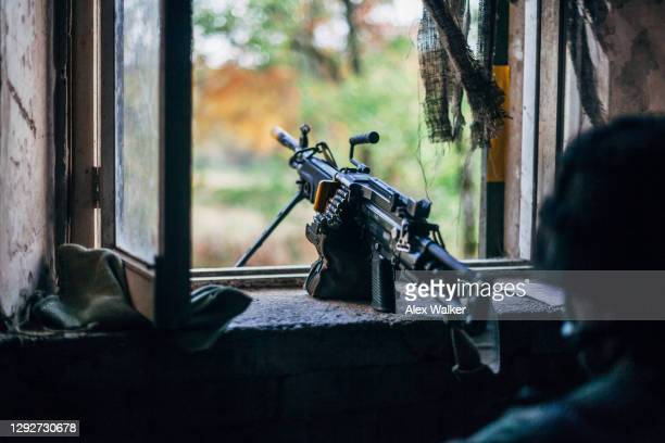 a light machine gun sentry post in an open window surrounded by camouflage netting. - gunman stock pictures, royalty-free photos & images