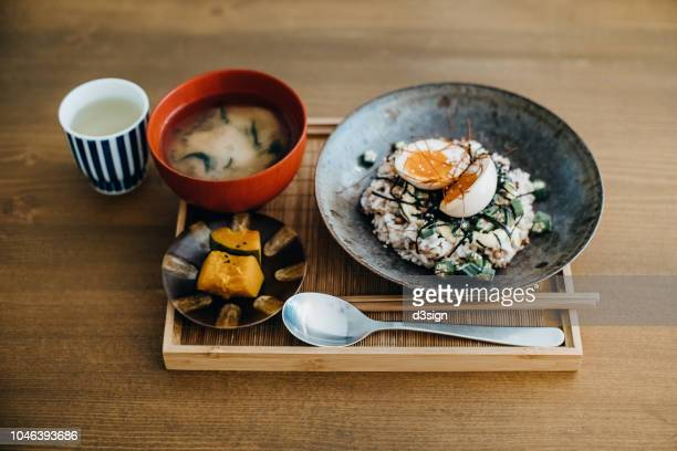 light meal of soft boiled egg over rice, stewed pumpkin, miso soup and tea freshly served in tray on table in a restaurant - japanese food stock pictures, royalty-free photos & images