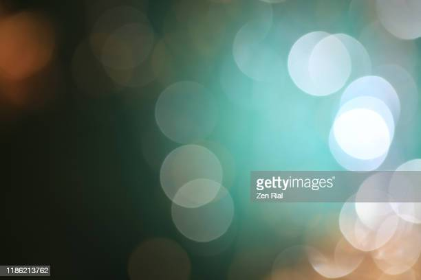 light orbs from defocused christmas decorations on greenish background - デフォーカス ストックフォトと画像