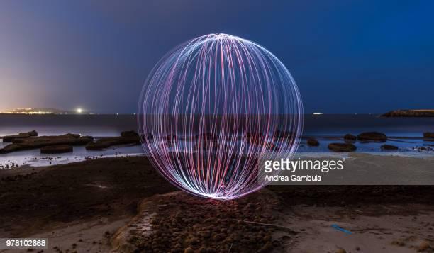 Light painted sphere on beach at night, Cagliari, Sardinia, Italy