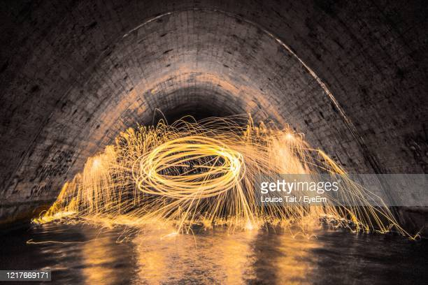 light painting in water filled tunnel - tunnel stock pictures, royalty-free photos & images