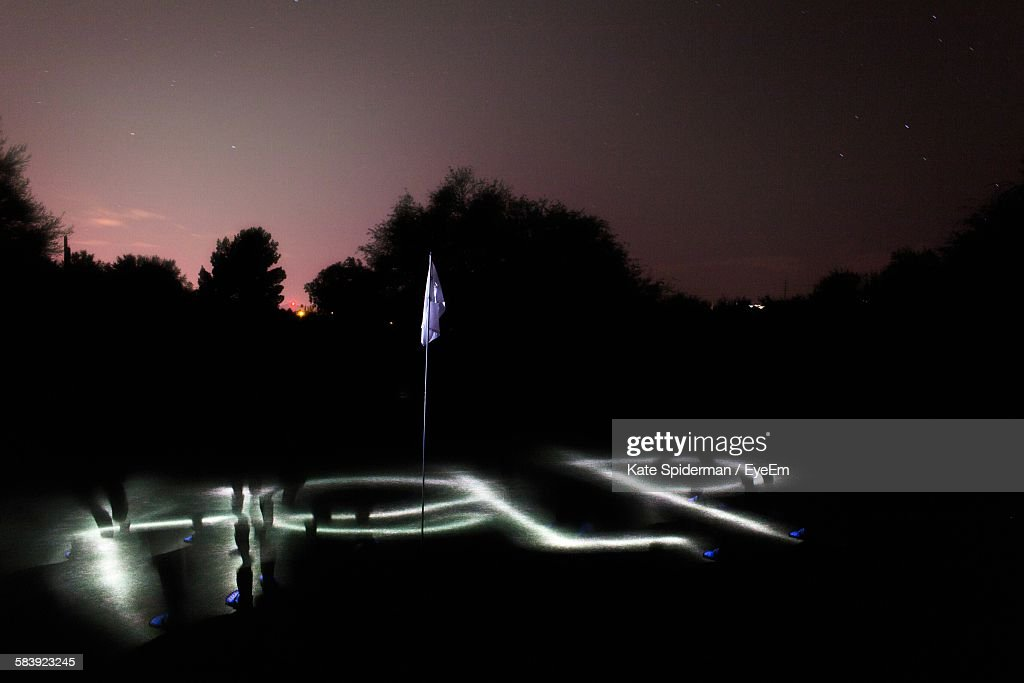 Light Painting On Golf Course By Silhouette Trees Against Sky Stock