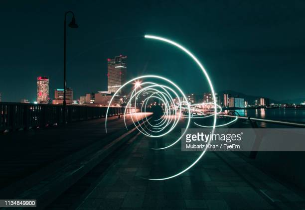 light painting on road against sky in city at night - lichtmalerei stock-fotos und bilder