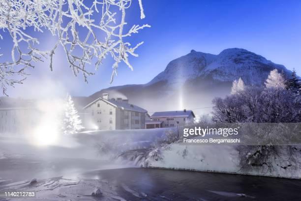 Light pillars phenomenon and fog along the Inn river. La Punt Engadine valley, Canton of Grisons, Switzerland, Europe.