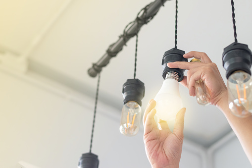 LED light Power saving concept. Asia man changing compact-fluorescent (CFL) bulbs with new  bulb. 1130699882
