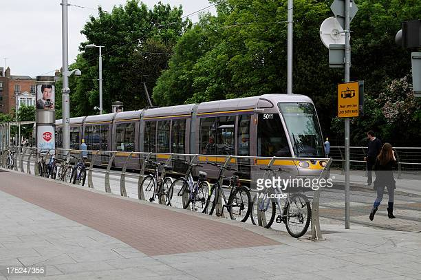 Light Railway transit system train at St Stephens Green Dublin Ireland Bicycles parked on the barrier