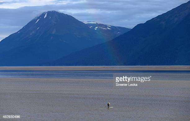 A light rainbow hits the water as a surfer waits to catch the Bore Tide at Turnagain Arm on July 16 2014 in Anchorage Alaska Alaska's most famous...