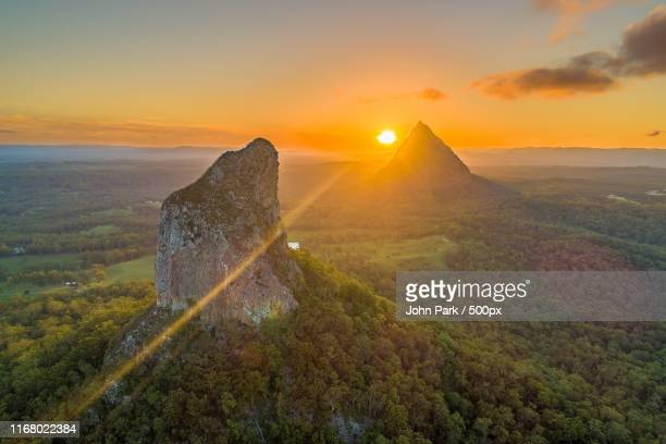 light ray firing through the glass house mountains - glass house mountains stock pictures, royalty-free photos & images