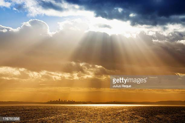 light rays from clouds above the city - zonnestraal stockfoto's en -beelden