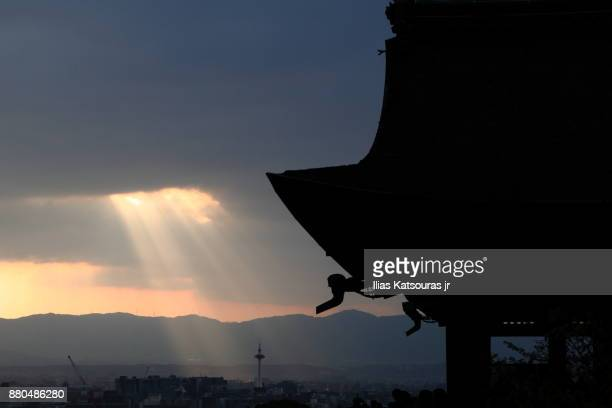 Light rays through thick clouds over Kyoto, with temple silhouette in the foreground