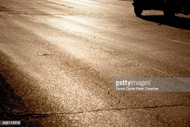 Luz reflejada en el camino, coche en movimiento en el fondo.
