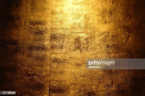 Light shining above a golden wall