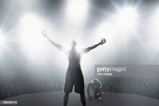 Light shining from behind winning African American MMA boxer