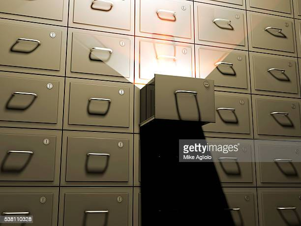 light shining from open file cabinet - mike agliolo stock pictures, royalty-free photos & images