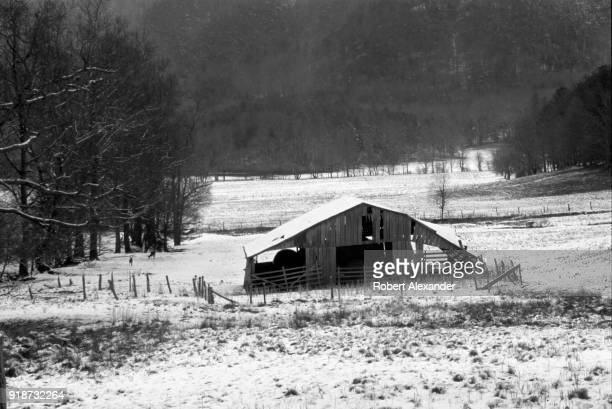 A light snow covers a barn and pastures in Cades Cove in the Great Smoky Mountains National Park in Tennessee