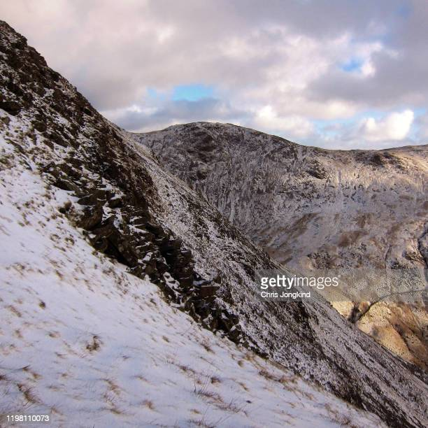 light snow on rugged mountain peaks - steep stock pictures, royalty-free photos & images