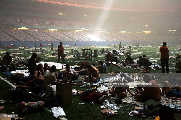 Light streaming down through the ceiling of the Superdome in New Orleans Louisiana illuminates a ragged crowd of refugees taking shelter at the arena...