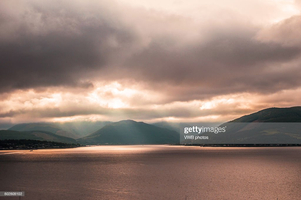Light streaming through clouds at sunset : Stock Photo