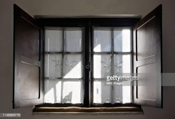 light streaming through lace curtains - fensterladen stock-fotos und bilder