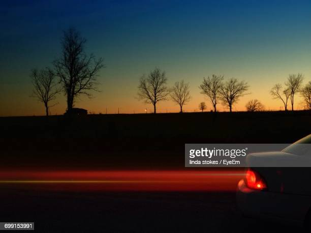 Light Trail Against Silhouette Bare Trees During Sunset