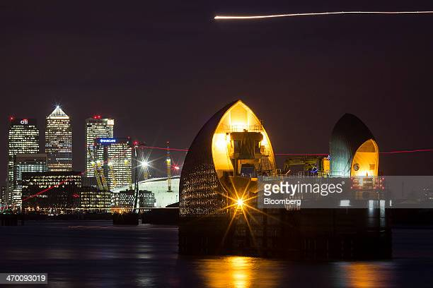 A light trail made by a passing aircraft is seen in the sky above a section of the Thames Barrier a flood defence system on the River Thames upriver...