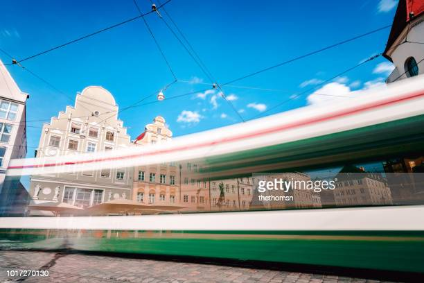 light trail of tram at historical downtown of augsburg, germany - augsburg stock-fotos und bilder