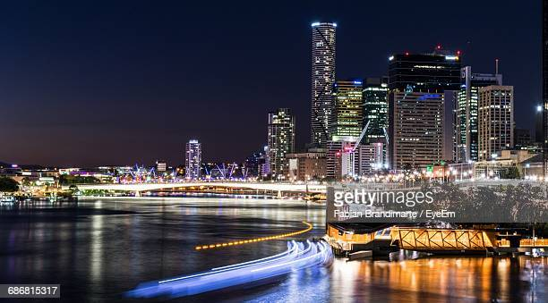 Light Trail On Brisbane River By Illuminated Skyscrapers Against Sky