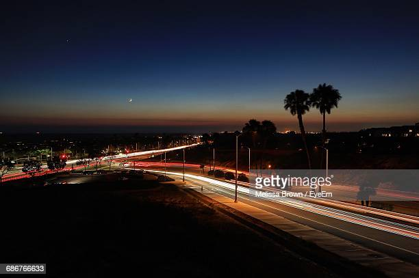 light trail on highway against sky at night - costa mesa stock photos and pictures
