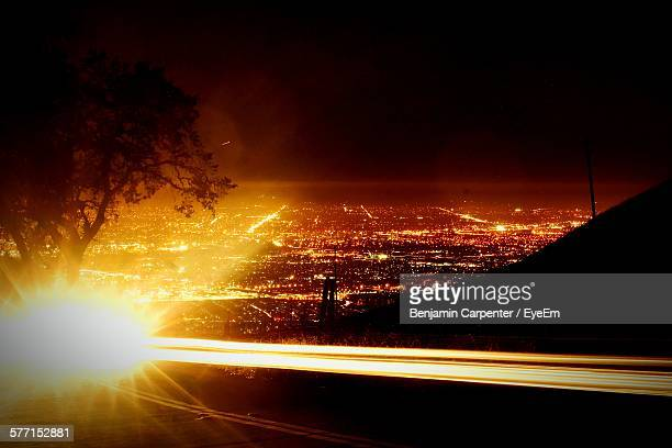 Light Trail On Road By Illuminated Landscape Against Clear Sky At Night