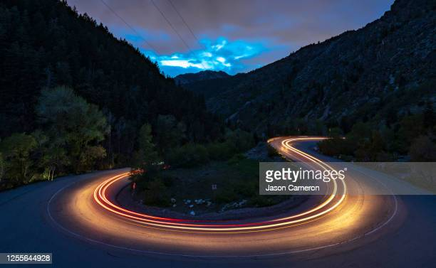 light trail s-curve mountain road at dusk - utah stock pictures, royalty-free photos & images