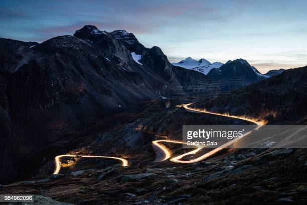 Light trails along a rural road in the mountains at dusk.