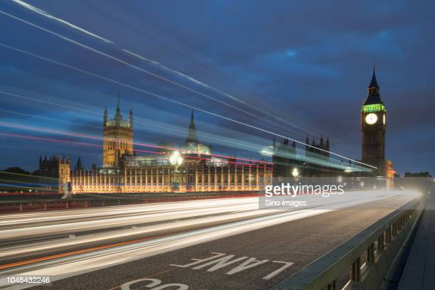 light trails along westminster bridge, big ben and houses of parliament in background, london, england, uk - image stock pictures, royalty-free photos & images