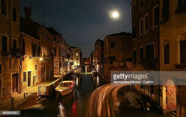 light trails and boats on canal amidst buildings in city at night - alessandro miccoli fotografías e imágenes de stock