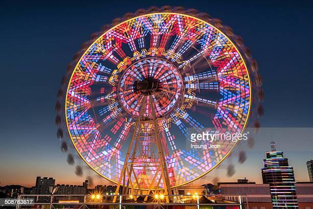 Light trails and Ferris wheel at night in Ulsan, South Korea.