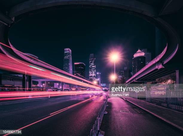 light trails at night on a main street in beijing. - straßenlaterne stock-fotos und bilder