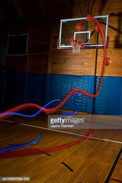 light trails behind basketballs above indoor basketball hoop (digital composite) - shooting baskets stock pictures, royalty-free photos & images