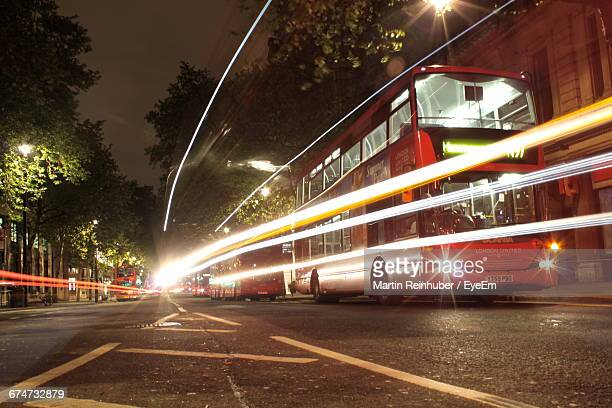 Light Trails By Buses On Street At Night
