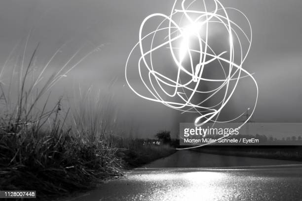 light trails by lake against sky at night - morten müller schnelle stock-fotos und bilder