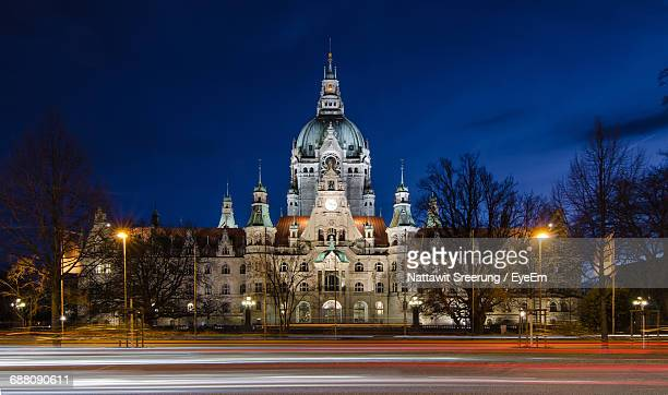 light trails by new town hall against sky at night - hanover germany stock pictures, royalty-free photos & images