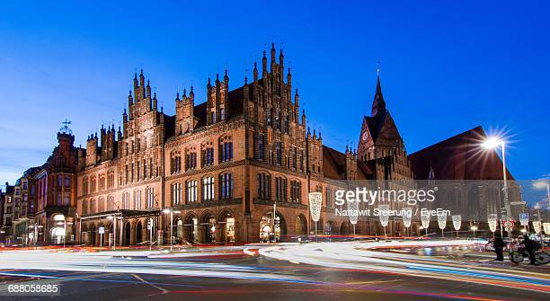 light trails by old church against sky at dusk - hanover germany stock pictures, royalty-free photos & images