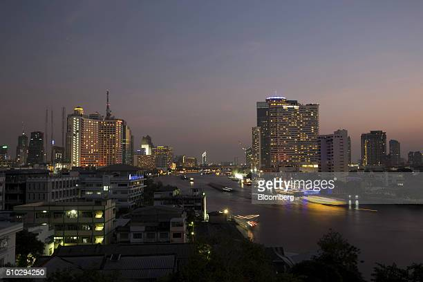 Light trails from boats run past illuminated commercial and residential buildings on the Chao Phraya river in this long exposure photograph taken at...