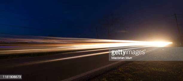 light trails from cars moving on a road - light trail stock pictures, royalty-free photos & images